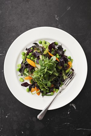 water cress: Mixed leaf salad with watercress, carrots and peas (seen from above)