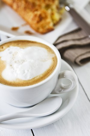 omzet: A cappuccino with milk foam and an apple turnover in the background LANG_EVOIMAGES