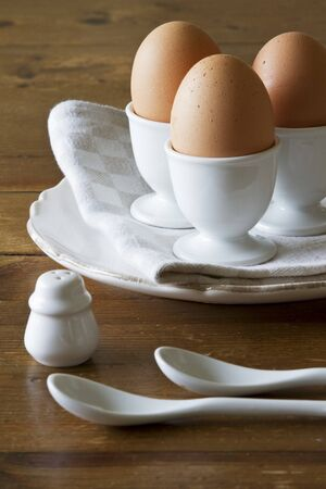 egg cups: Three brown eggs in white porcelain egg cups