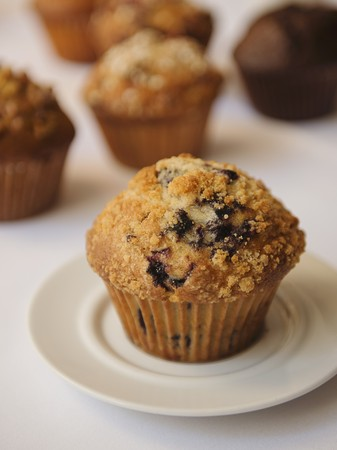 blueberry muffin: A blueberry muffin with assorted muffins in the background