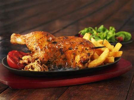 pollos asados: La mitad de un pollo asado con papas fritas, aros de cebolla y tomates