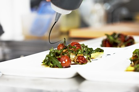 drizzle: Tomato salad with rocket being drizzled with balsamic vinegar LANG_EVOIMAGES