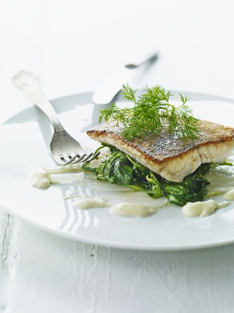 fish fillet: A fish fillet on a bed of spinach for Easter