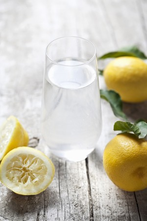 lemon water: A glass of lemon water and fresh lemons