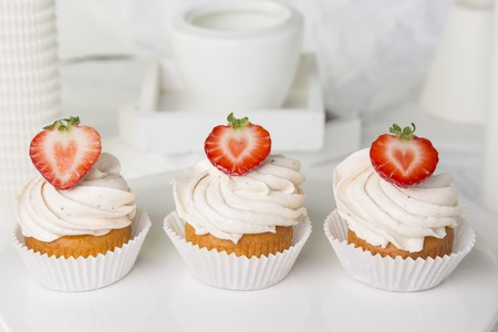 buttercream: Three strawberry cupcakes topped with buttercream LANG_EVOIMAGES