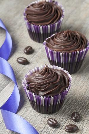 ganache: Three chocolate ganache cupcakes with chocolate beans and a ribbon