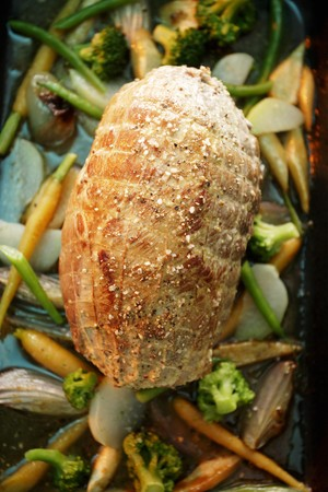 kohl: A whole roast pork roulade on a bed of vegetables in a roasting tin LANG_EVOIMAGES