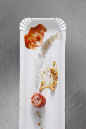 leavings: Left over sausage, ketchup and mustard on a paper plate