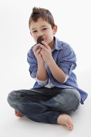 Kleiner Junge isst einen Schokokuss LANG_EVOIMAGES