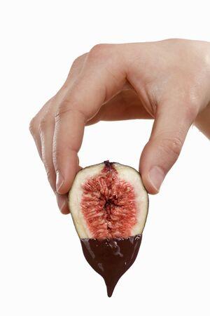 chocolate derretido: Mano que sostiene un higo goteo con chocolate derretido