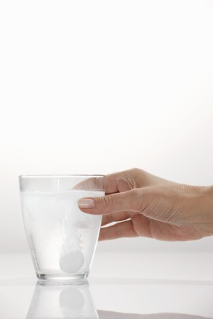 fizzy tablet: A hand holding a glass with an effervescent tablet LANG_EVOIMAGES