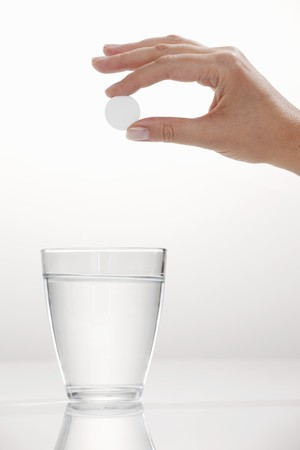 fizzy tablet: A hand holding an effervescent tablet over a glass LANG_EVOIMAGES