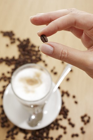 hot coffees: Fingers holding a coffee bean over a glass of Latte Machhiato