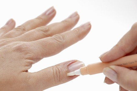 handcare: A woman applying a care product to her nail bed