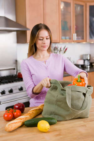 worktops: Woman Unloading Groceries from Cloth Bag on Kitchen Counter