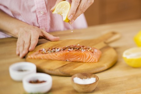 lemon wedge: Woman Squeezing a Lemon Wedge over Salmon