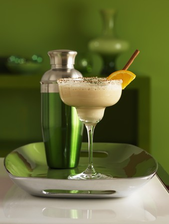 martini shaker: Frozen martini in a glass with sugar on the rim of the glass and a shaker