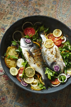 dorade: Dorade Fish Cooked in a Skillet with Tomatoes, Lemons and Parsley
