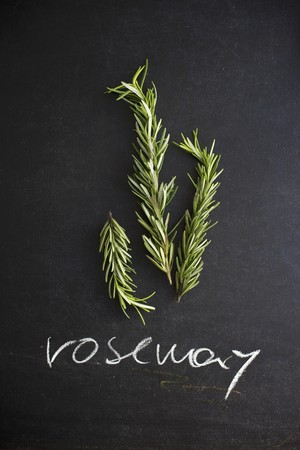 sprigs: Fresh Rosemary Sprigs on a Chalk Board with the Word Rosemary Written in Chalk