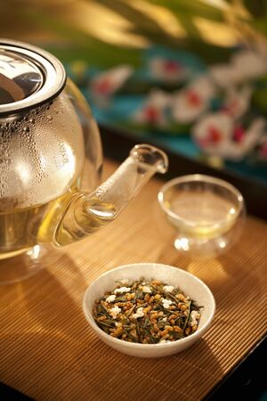 sencha tea: Japanese Genmaicha Tea in a Bowl with Clear Glass Tea Pot and Cup; On Bamboo Tray LANG_EVOIMAGES