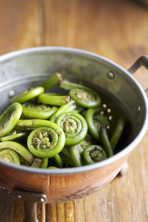 soft furnishing: Colander of Fiddleheads on a Wooden Table