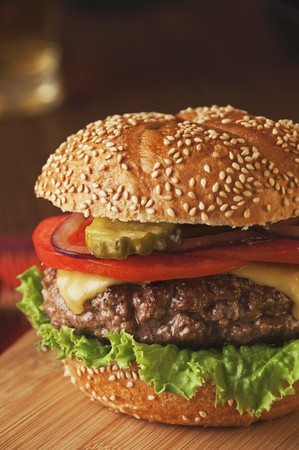 sesame seed bun: Juicy Cheeseburger with Tomato, Onion and Pickle on Sesame Seed Bun