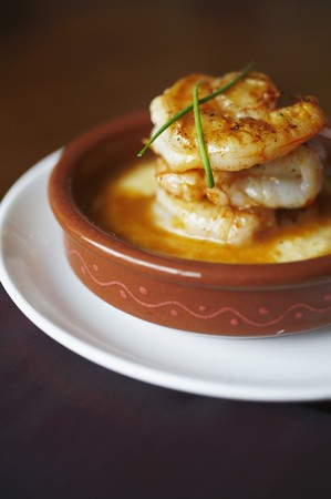 grits: Shrimp and Grits in a Brown Dish with Chive Garnish