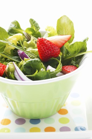 arugola: Spring salad with red onions and strawberries in bowl
