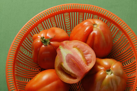 redness: Fresh tomatoes in red bowl (close-up)