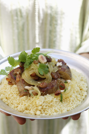made in morocco: Person serving lamb ragout with almonds, raisins, couscous