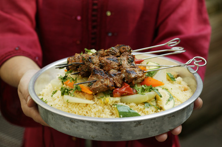 couscous: Person serving kebabs with vegetables and couscous