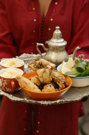 couscous: Woman serving chicken with couscous, beans and lentils