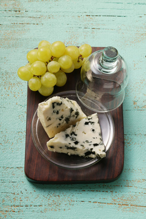 greenish blue: Roquefort with cheese dome and green grapes on chopping board