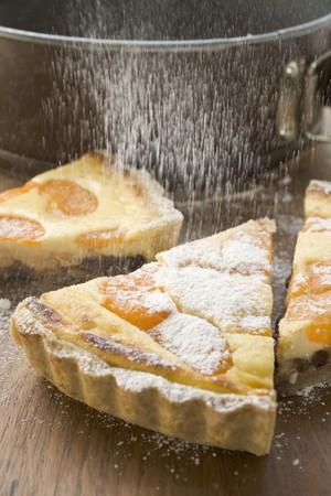sprinkling: Sprinkling apricot tart with icing sugar LANG_EVOIMAGES
