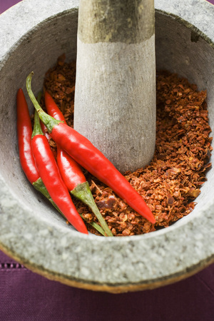 crushed red peppers: Chili peppers and chili powder in mortar (close-up)