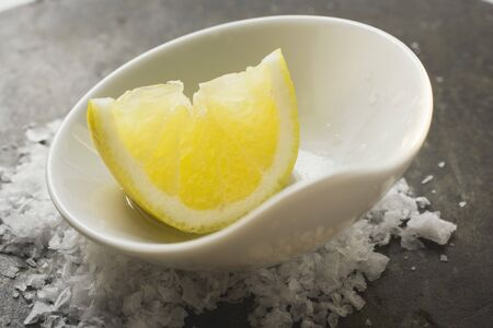 lemon wedge: Lemon wedge with olive oil in a small bowl on salt