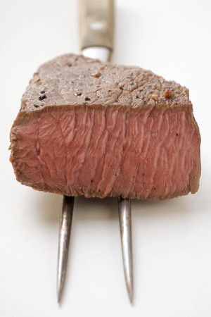 cut off: Beef steak, a piece cut off, on meat fork LANG_EVOIMAGES