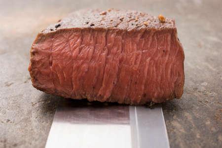 cut off: Beef steak, a piece cut off, on Asian knife