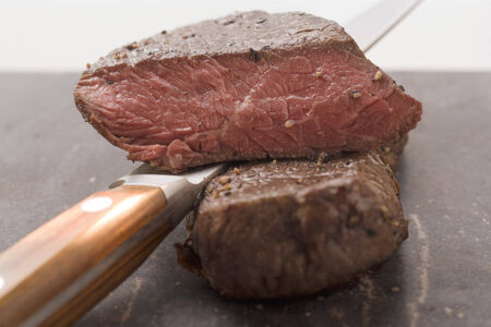 cut off: Beef steaks, one with a piece cut off, with knife LANG_EVOIMAGES