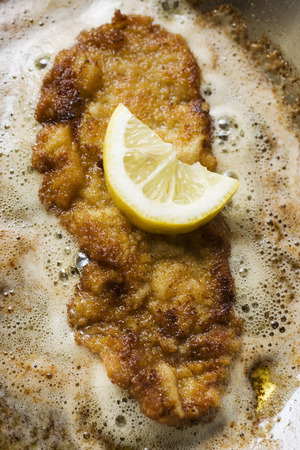 pan tropical: Frying escalope with lemon in frying pan