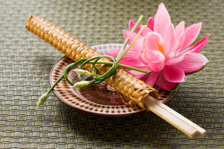 nymphaea odorata: Chopsticks in woven wrapper with water lily on plate LANG_EVOIMAGES