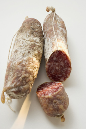 cut off: Two whole Italian salamis, one with a piece cut off