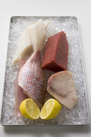 tunafish: Assorted fish fillets with lemon on ice