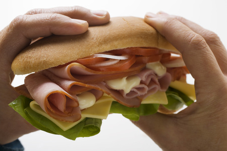 sub sandwich: Hands holding ham and cheese sub sandwich LANG_EVOIMAGES