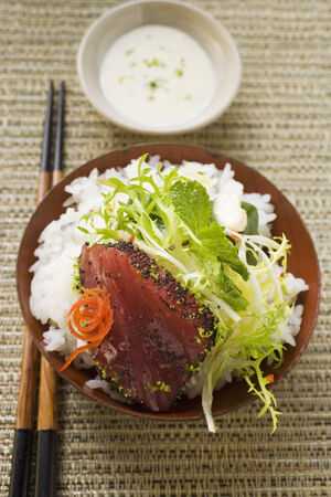 tunafish: Raw tuna fillet with poppy seeds, rice and salad