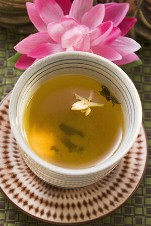 nymphaea odorata: Jasmine tea in small bowl in front of water lily