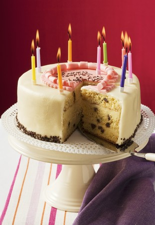 ignited: Birthday cake with burning candles, a piece cut