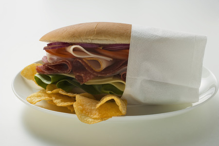 crisps: Salami, ham, cheese and salad sandwich in napkin with crisps LANG_EVOIMAGES