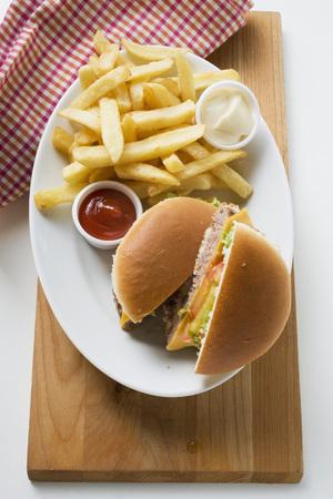 all american burger: Cheeseburger, chips, mayonnaise, ketchup on plate LANG_EVOIMAGES