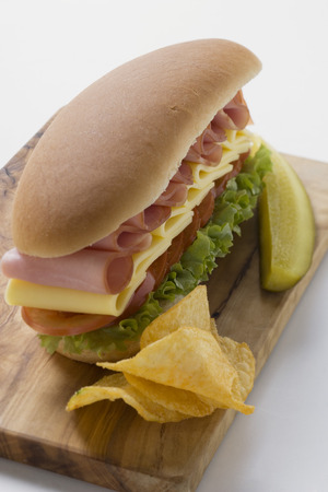 hero sandwich: Sub sandwich with crisps and gherkin on chopping board LANG_EVOIMAGES